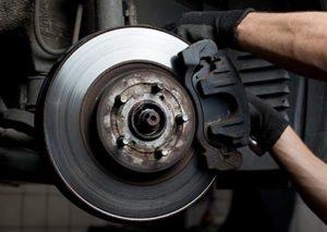 Car Mechanic Working on Brake Pad